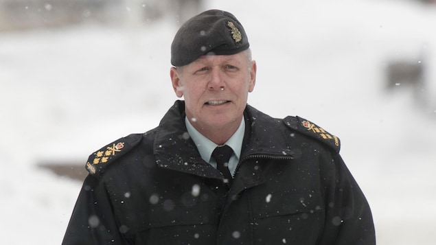Un homme marche sous la neige, il est vêtu d'un manteau à épaulettes de l'armée et d'un béret assorti.