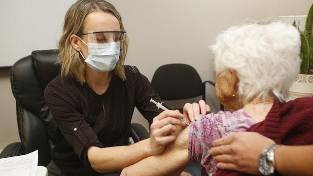 Une femme portant un masque et une visière administre un vaccin à une femme âgée.