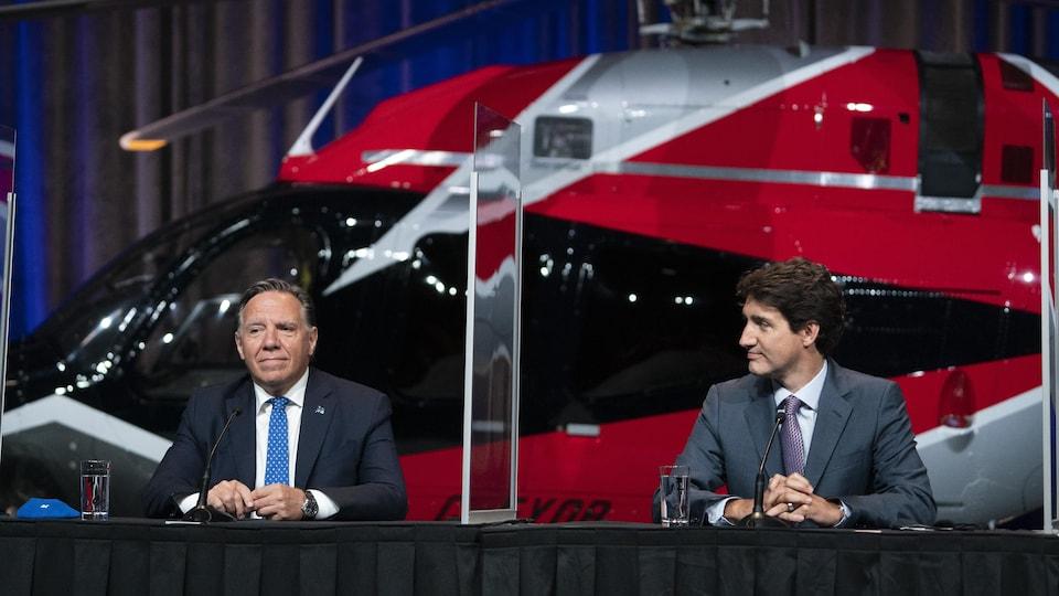 François Legault et Justin Trudeau sont assis à la table de presse devant un gros hélicoptère rouge.