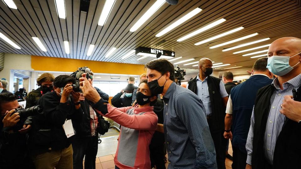M. Trudeau, de profil, se fait prendre en photo (égoportrait) aux côtés d'une femme. Les deux sourient et portent le masque. Ils sont entourés de gardes de sécurité et de journalistes.