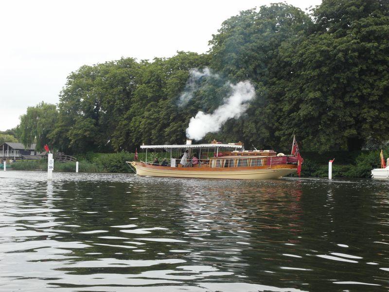 Long yacht fin , coque crème et bois, drapeau anglais, panache de vapeur