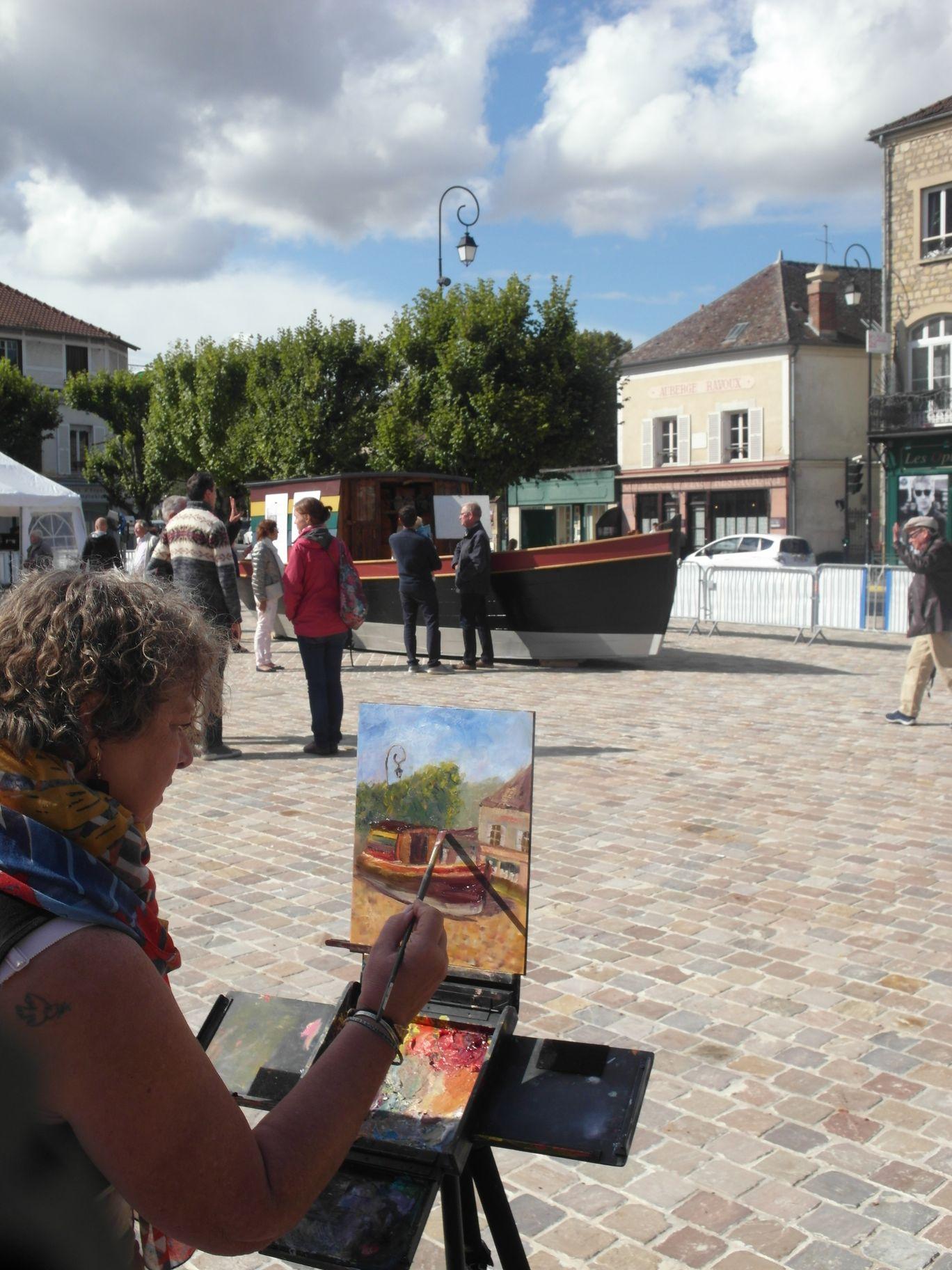 un artiste est en train de peindre le bateau sur l aplace de l'hotel de ville