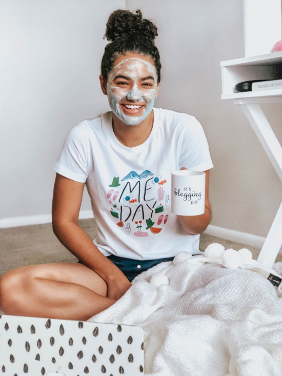 "Girl with curly hair wearing a white t-shirt that says ""Me Day"", a blue face mask, and a mug that says ""It's Blogging Day"""