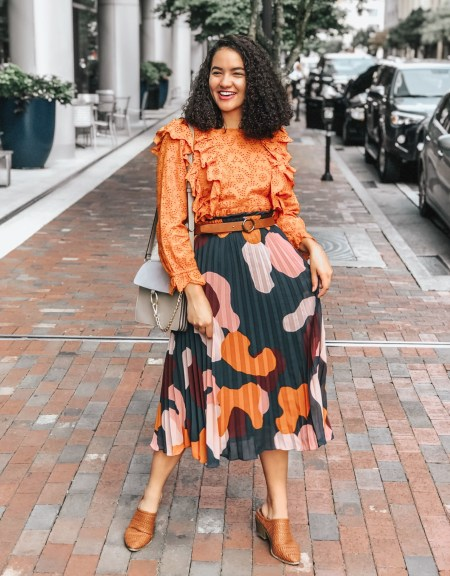 Girl with curly hair wearing an orange printed blouse from Rent the Runway, a printed and patterned skirt from ASOS, a pair of brown mules and a brown belt from Target, and a crossbody bag from Amazon.