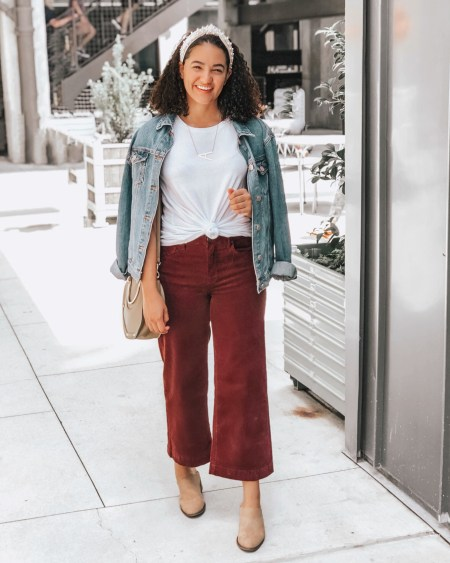 Girl with curly hair wearing a plain white tee, maroon wide leg pants from lulus, brown booties from american eagle, a denim jacket from forever 21, a saddle bag from tjmaxx, an initial necklace from amazon, and a pearl headband from amazon.