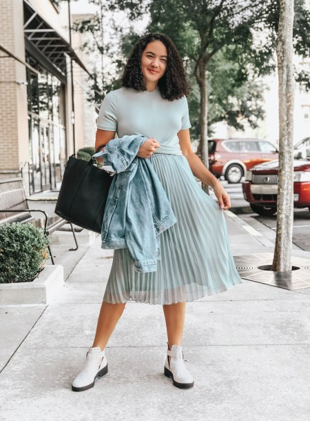 Girl with curly hair wearing a teal crop top, a teal pleated midi skirt, a denim jacket, a black tote bag, and military boots from H&M