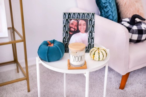 Side table with a Rae Dunn candle that says