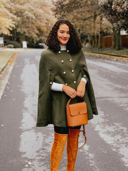 Girl with curly hair wearing a green cape from Chicwish, faux leather leggings, a white mock neck sweater, and brown booties.