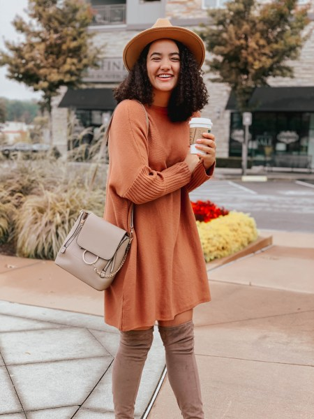 Girl with curly hair wearing an orange sweater dress, taupe over the knee boots, a tan panama hat, and a taupe ring crossbody bag.