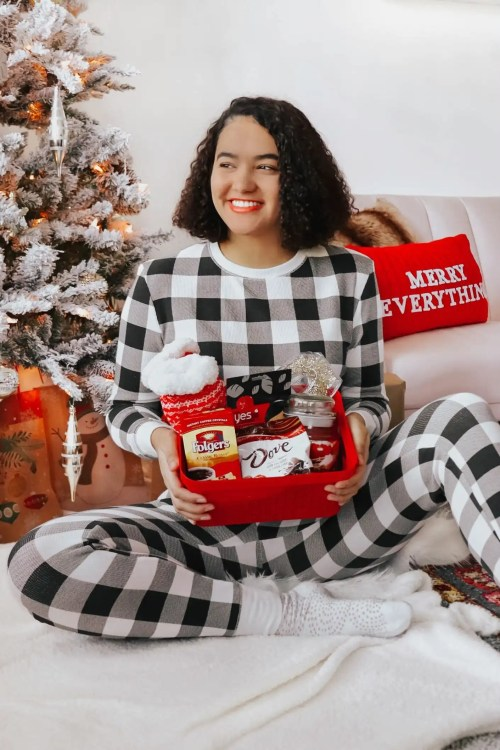 Girl with curly hair wearing gingham pajamas. She is holding a gift basket and is in front of a Christmas Tree.
