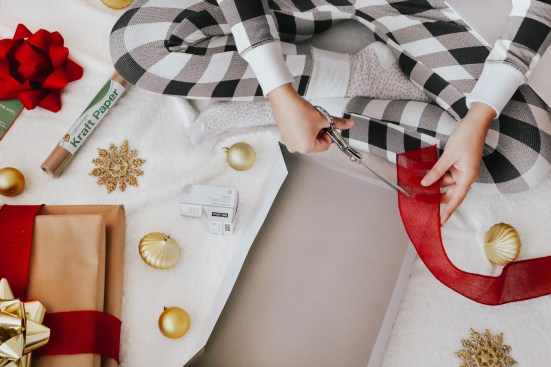 Girl wrapping Christmas gifts with gift wrapping items from Dollar General.