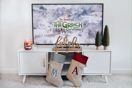 """Tv stand with tv on top of it. There is a candle, two fake felt trees, a stocking holder that says """"falala"""" and has two stockings on it."""