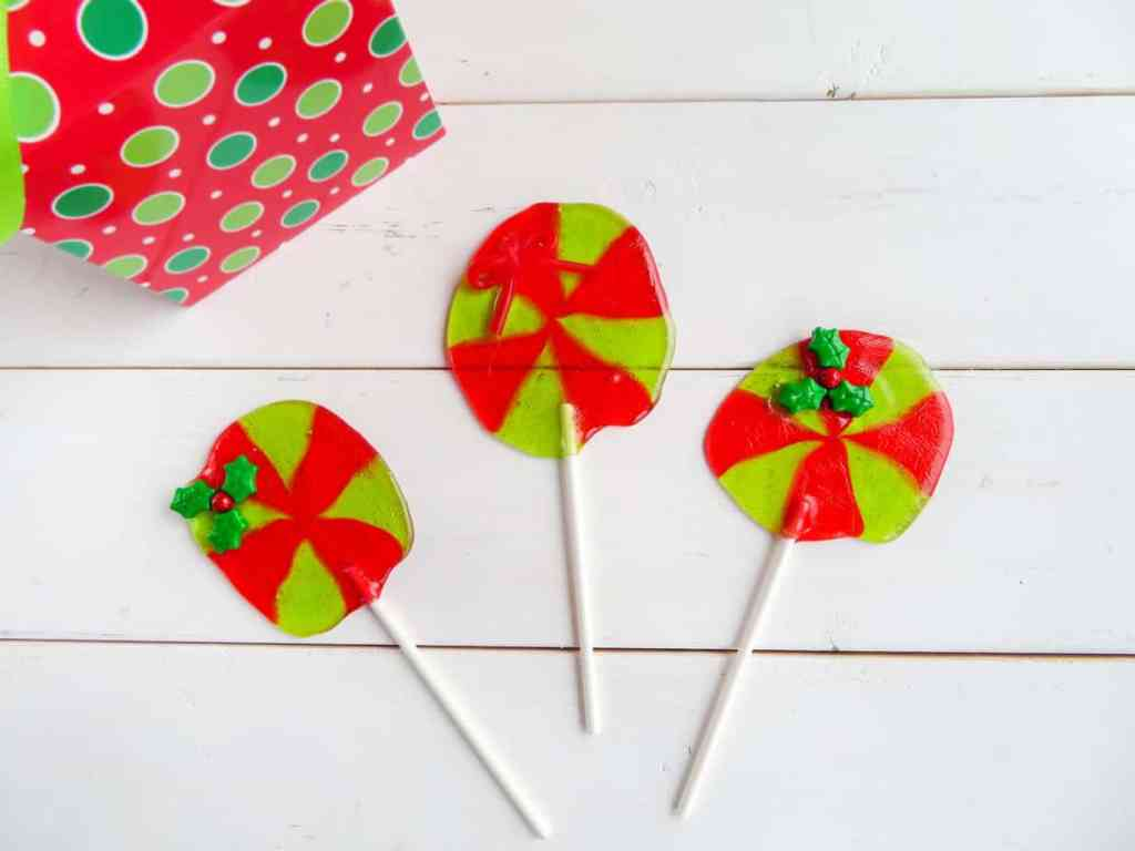 Three Red and green jolly rancher suckers with a holly leaf on two of them with a polka dotted box in the background to match.