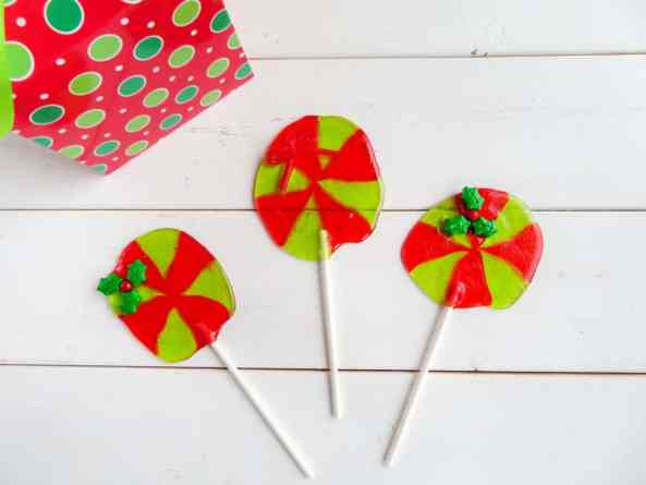red and green jolly rancher suckers with a candy holly leaf at the top on a white table with a present in the background