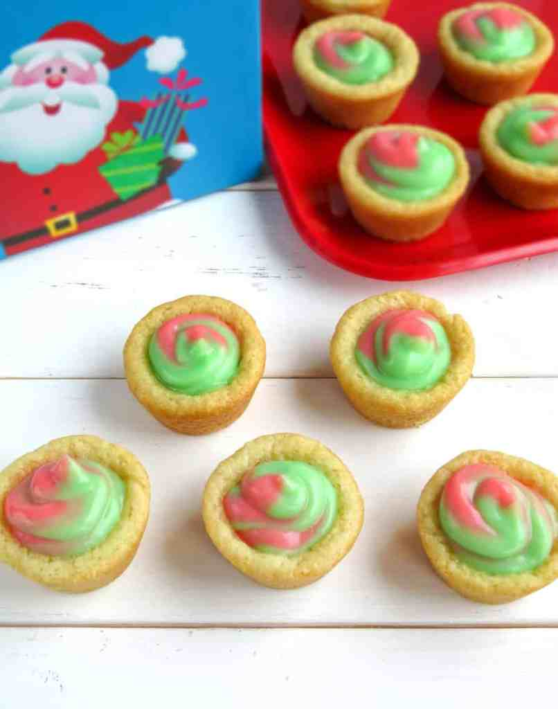 Green and red pudding in a mini pastry cup with a picture of Santa Claus in the background.