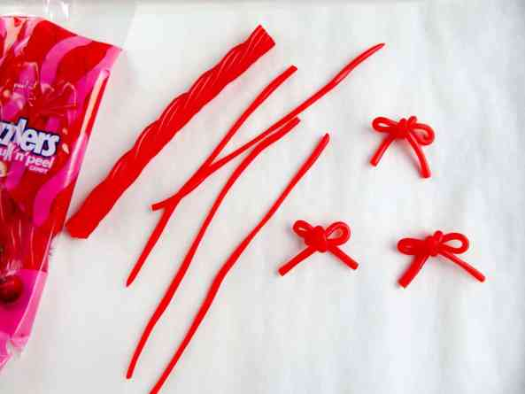a bag of twizzlers, twizzlers separated into strands and then tied into bows on a white paper