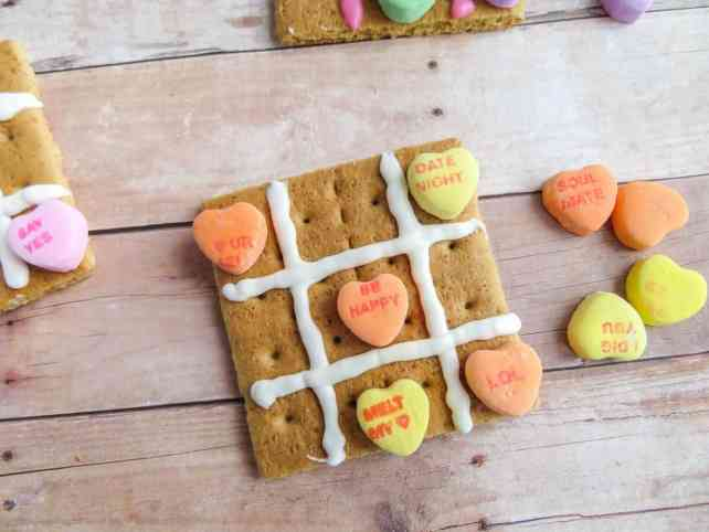three graham crackers with pink or white frosting on it and candy conversation hearts to look like a tic tac toe board on a wood table with more candy next to it