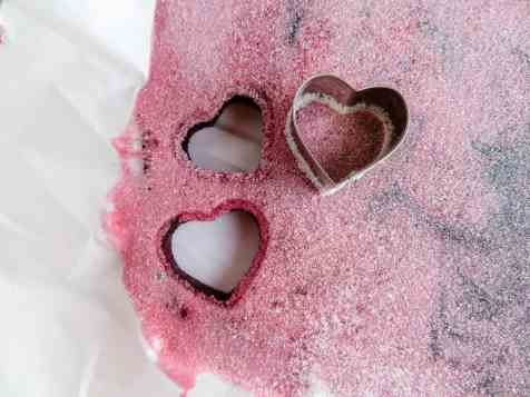 a heart cookie cutter cutting out pieces from the gummy mixture on a white background