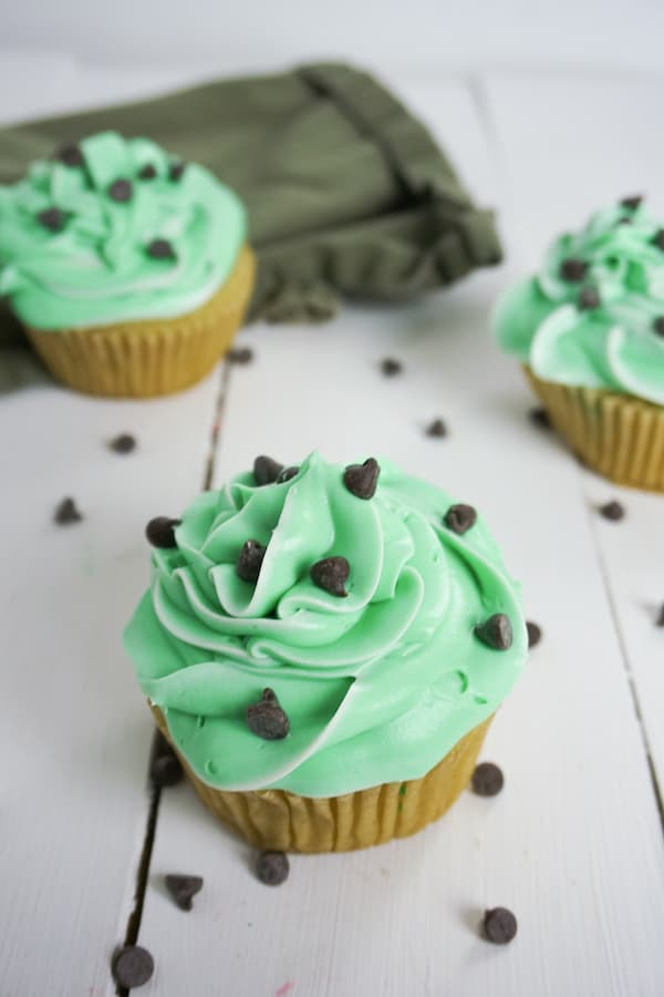 overhead view of three boozy andes mint cupcakes with chocolate chips on a white table and a green linen in the background