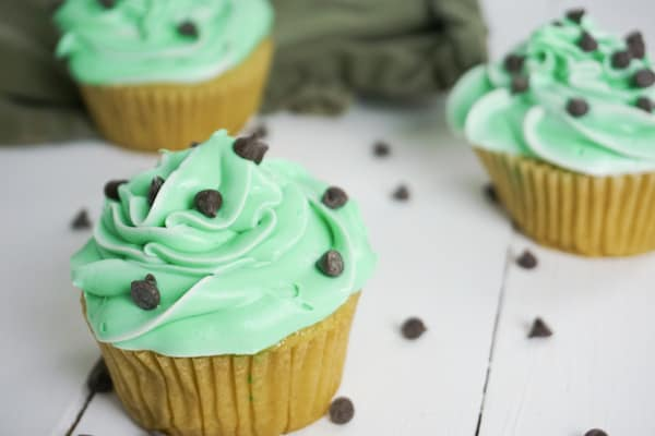 side view of three drunk cupcakes with chocolate chips on a white table and a green linen in the background