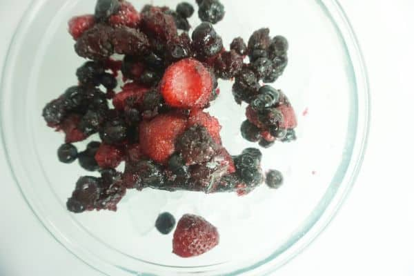 corn syrup and frozen berries in a glass bowl on a white table