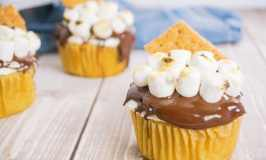 side view of three smores cupcakes on a wood table with a blue linen in the background