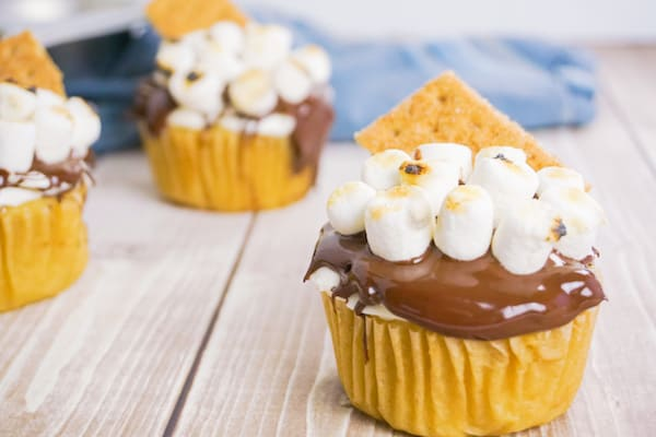 side view of three cupcakes frosted with chocolate frosting topped with marshmallows and a graham cracker on a wood background with a muffin tin and blue linen in the background