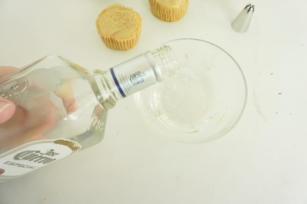tequila being poured into a glass bowl with cupcakes and a decorating tip in the background on a white table