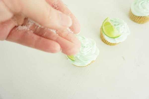 hand sprinkling salt onto margarita cupcakes on a white table