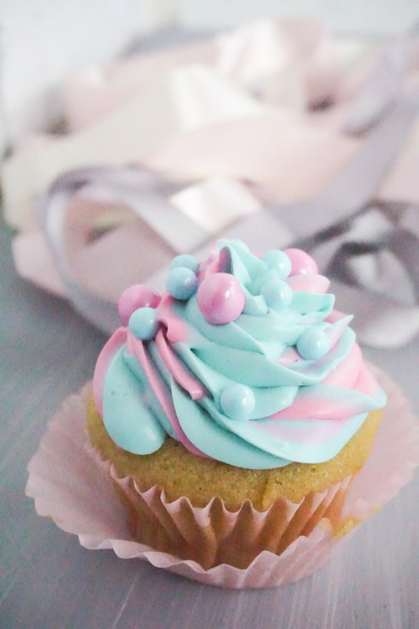 side view of single disney princess cupcakes with pink and blue large sugar pearls on a grey table with white pink and grey ribbons in the background