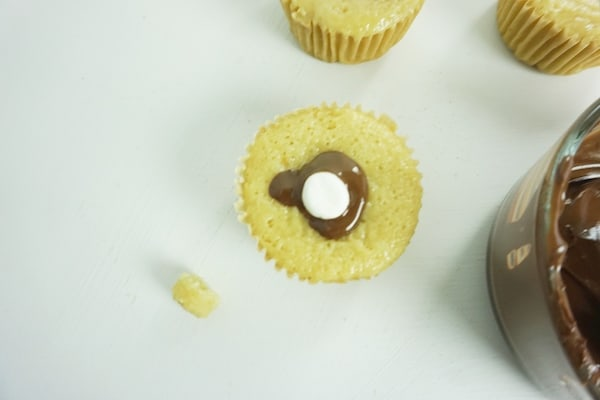 chocolate oozing out of the top of a cupcake around a mini-marshmallow stuffed into a well in the cupcake