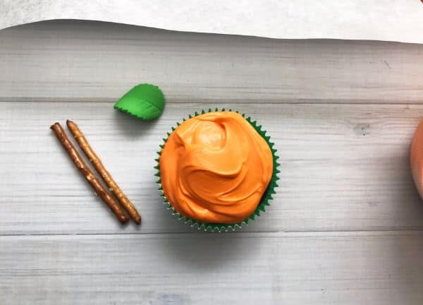 a cupcake topped with orange frosting next to two pretzel sticks and a candy leaf on a wood table
