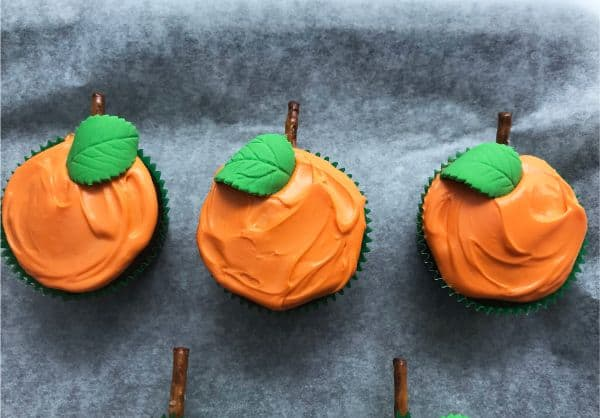 cupcakes decorated with orange frosting, green candy leaf, and pretzel stem to look like pumpkins on parchment paper