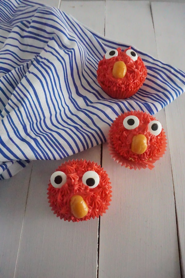 three cupcakes made to look like Elmo with red frosting, candy eyes and an orange starburst as a nose, on a wood table and a white and blue striped linen