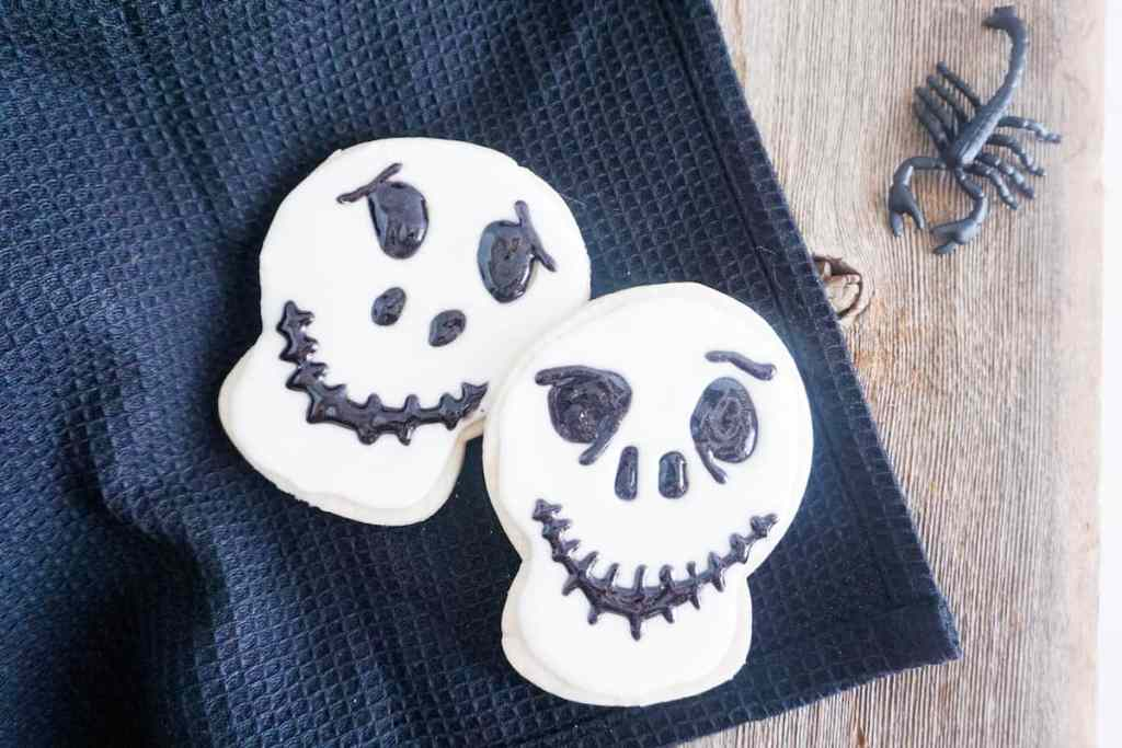 two cookies decorated with white frosting and black gel to look like Jack Skellington on a black linen on a wood table with a fake scorpion  next to it