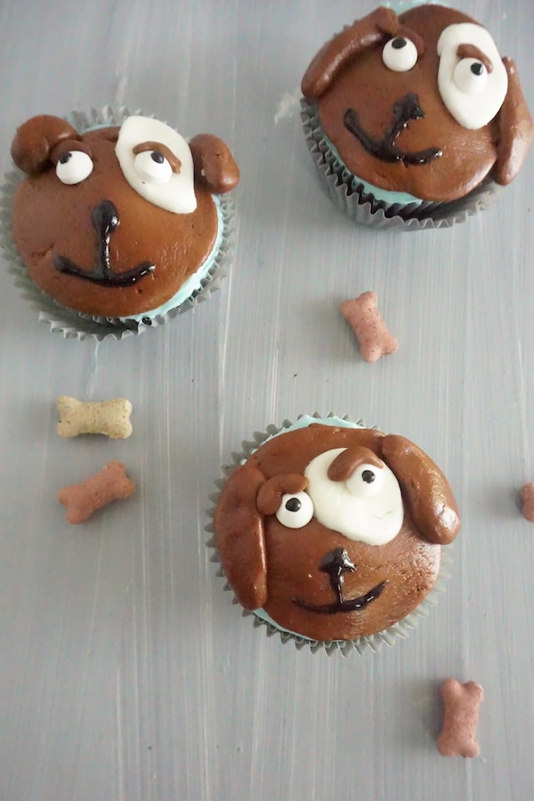 cupcakes topped with brown, white and block frosting to look like the face of a dog next to dog bone treats on a table