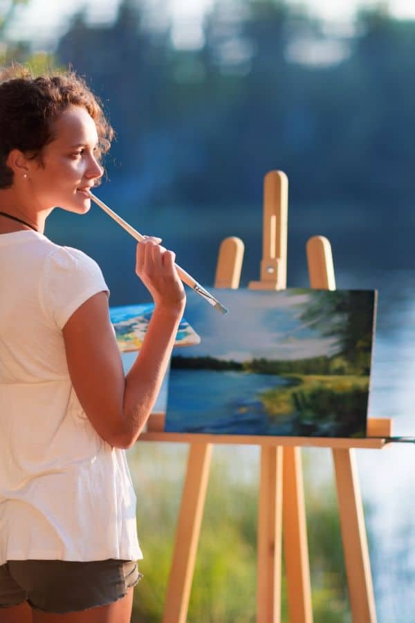 Woman painting next to river, holding paintbrush end against lower lip pondering
