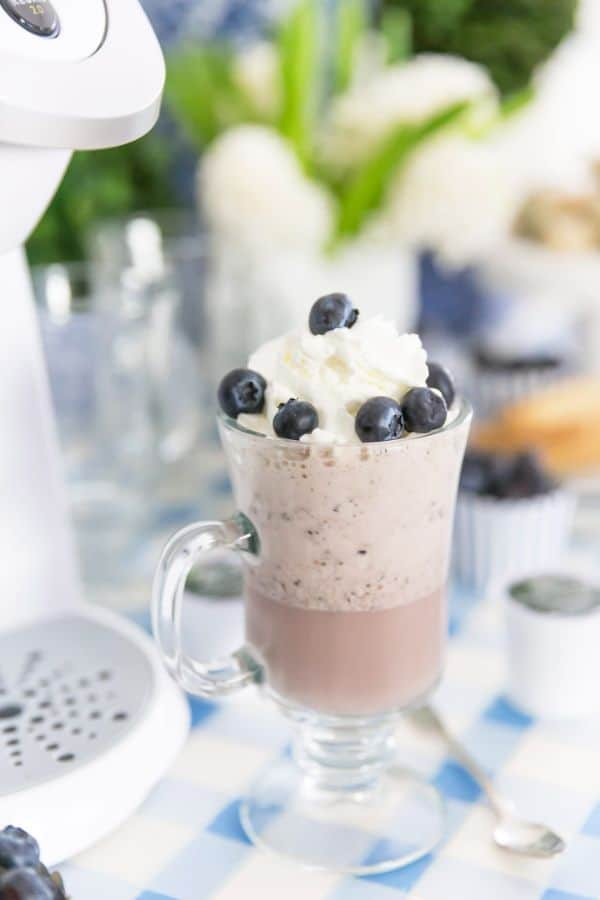 Blueberry frappuccino in a glass mug topped with whipped cream and blueberries with a coffee maker in the background on a blue checkered tablecloth