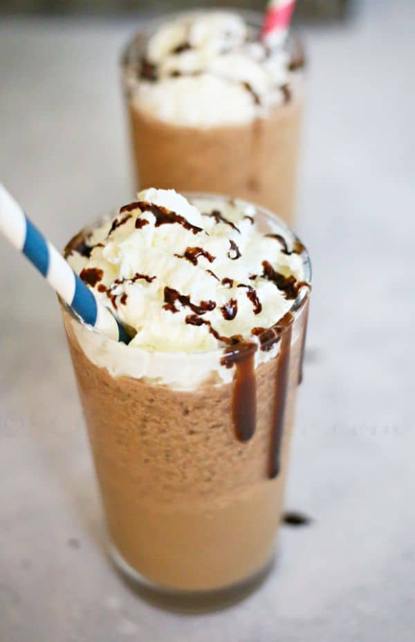 Reeses frappuccino topped with whipped cream and chocolate sauce with a blue and white straw and another drink in the background