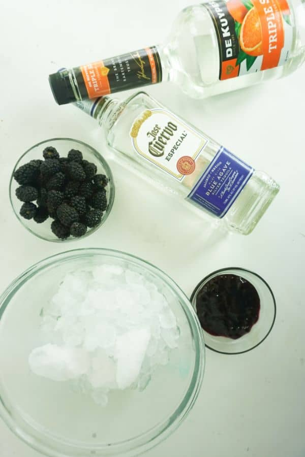 ingredients for making a blackberry margarita (ice, blackberries, blackberry jam, tequila and triple sec) on a white background