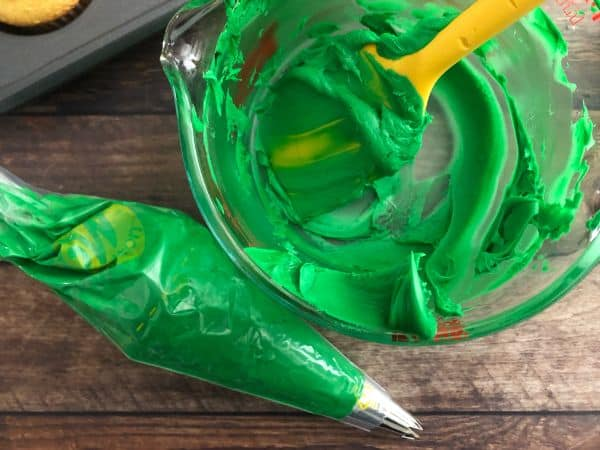 Green frosting in a glass bowl with a yellow spoon inside with a frosting bag next to it and a cupcake tin in the background.