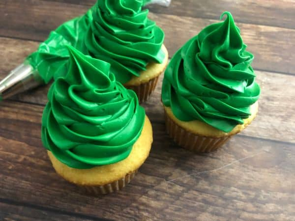 Three cupcakes with green frosting on top in the shape of a Christmas tree with a frosting bag in the background.