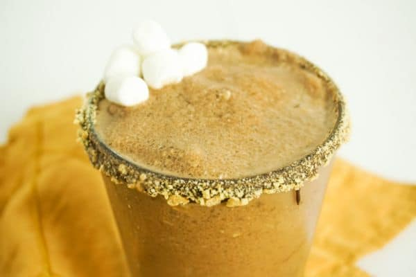 closeup of s'mores margarita in glass on orange dish towel, glass rimmed with chocolate and graham cracker crumbs, drink garnished with mini marshmallows