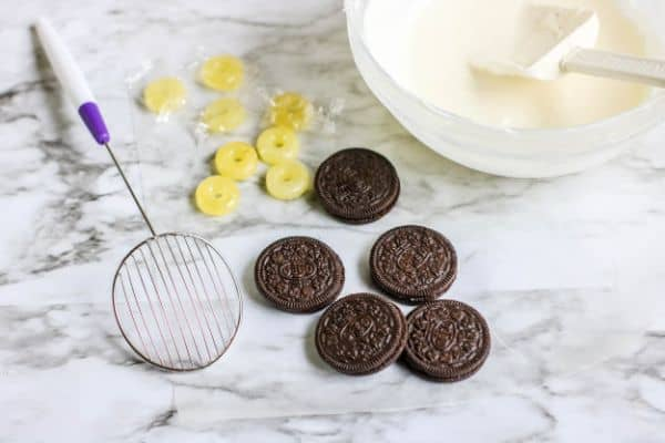 a bowl of melted white chocolate with a spatula in it next to yellow lifesavers. oreos and a strainer on a kitchen counter