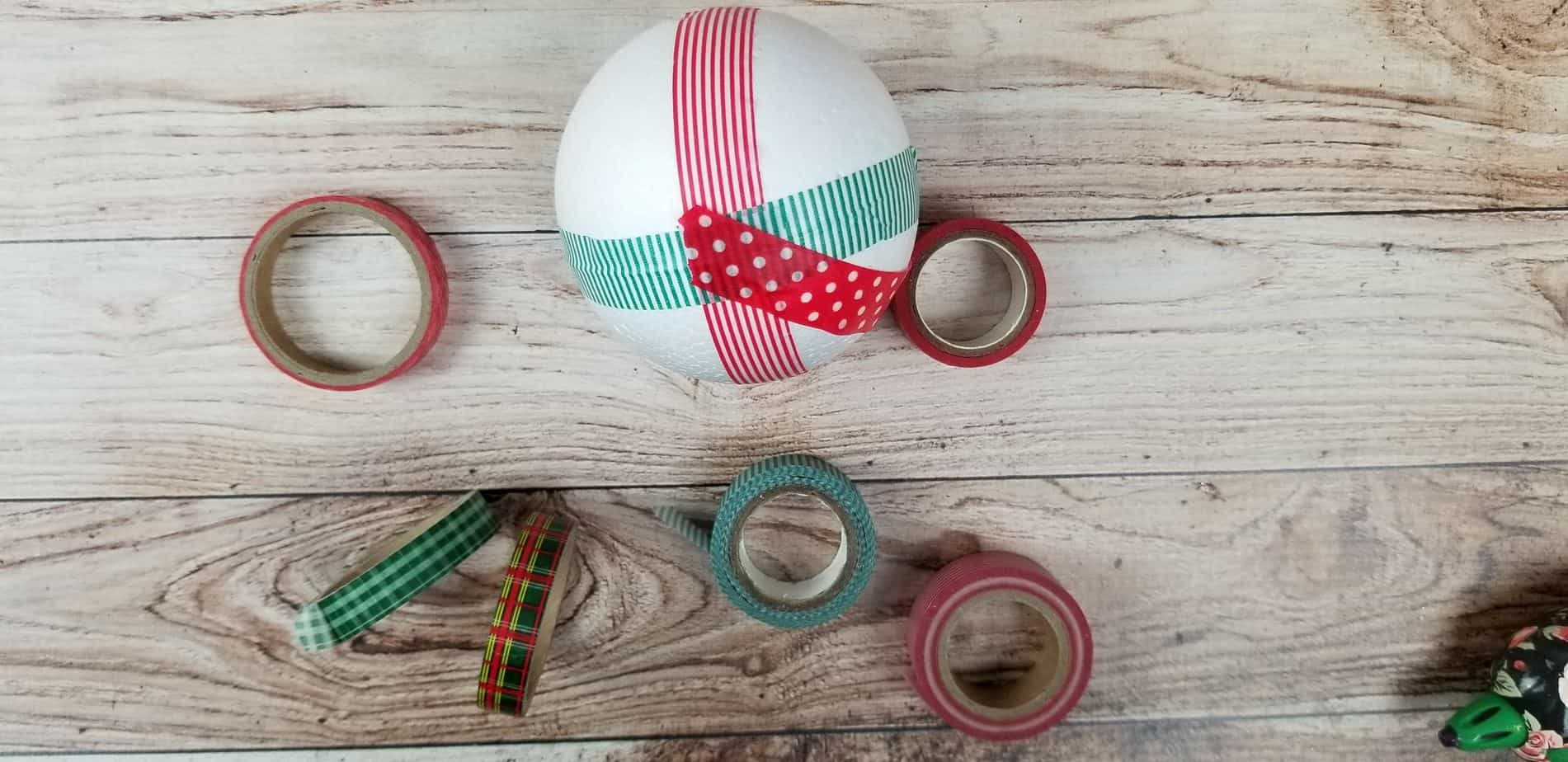a styrofoam ball wrapped with some red and green washi tape with more washi tape rolls on the wooden table