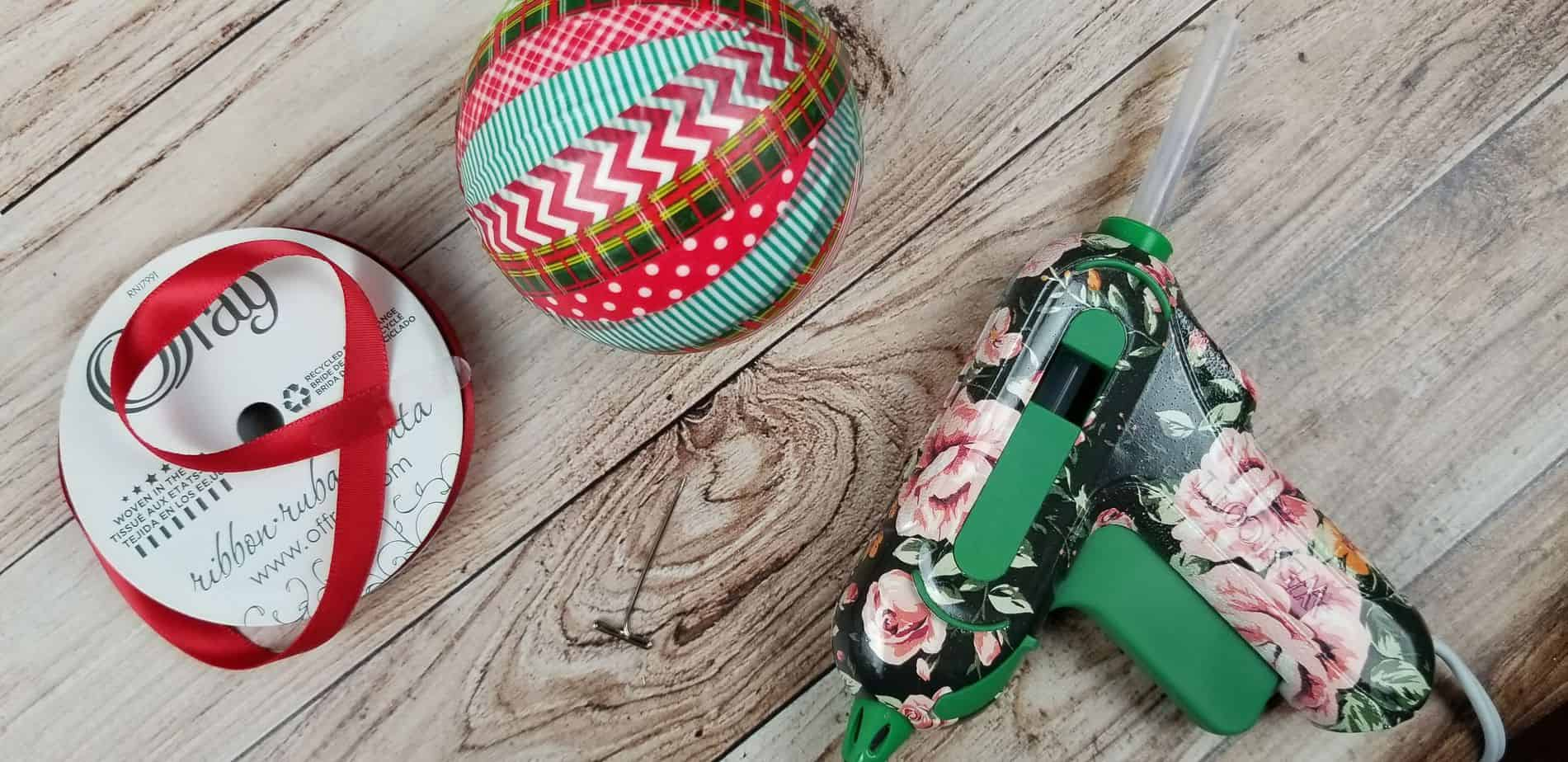 an ornament wrapped in red and green washi tape next to some red ribbon and a hot glue gun on a wooden table