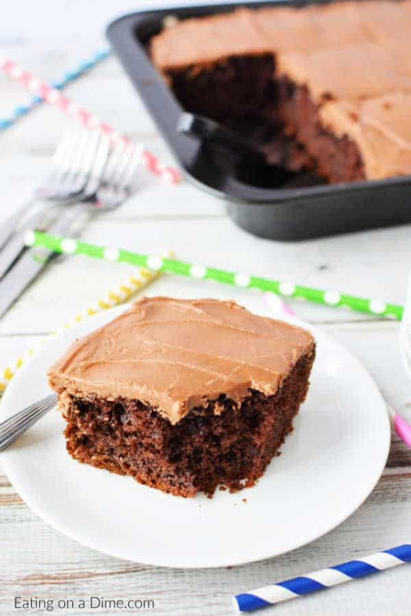 cola chocolate cake on a white plate next to colored straws with the rest of the cake in a baking pan in the background