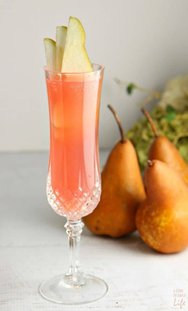 Cranberry Pear Prosecco Cocktail in a glass topped with three slices of pear on a white table with more pears in the background