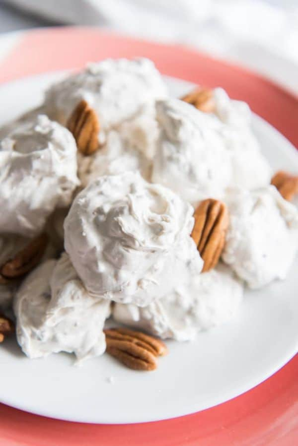 divinity candy and pecans on a white plate on a red background