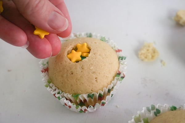a hand putting star sprinkles in the middle of a cupcake
